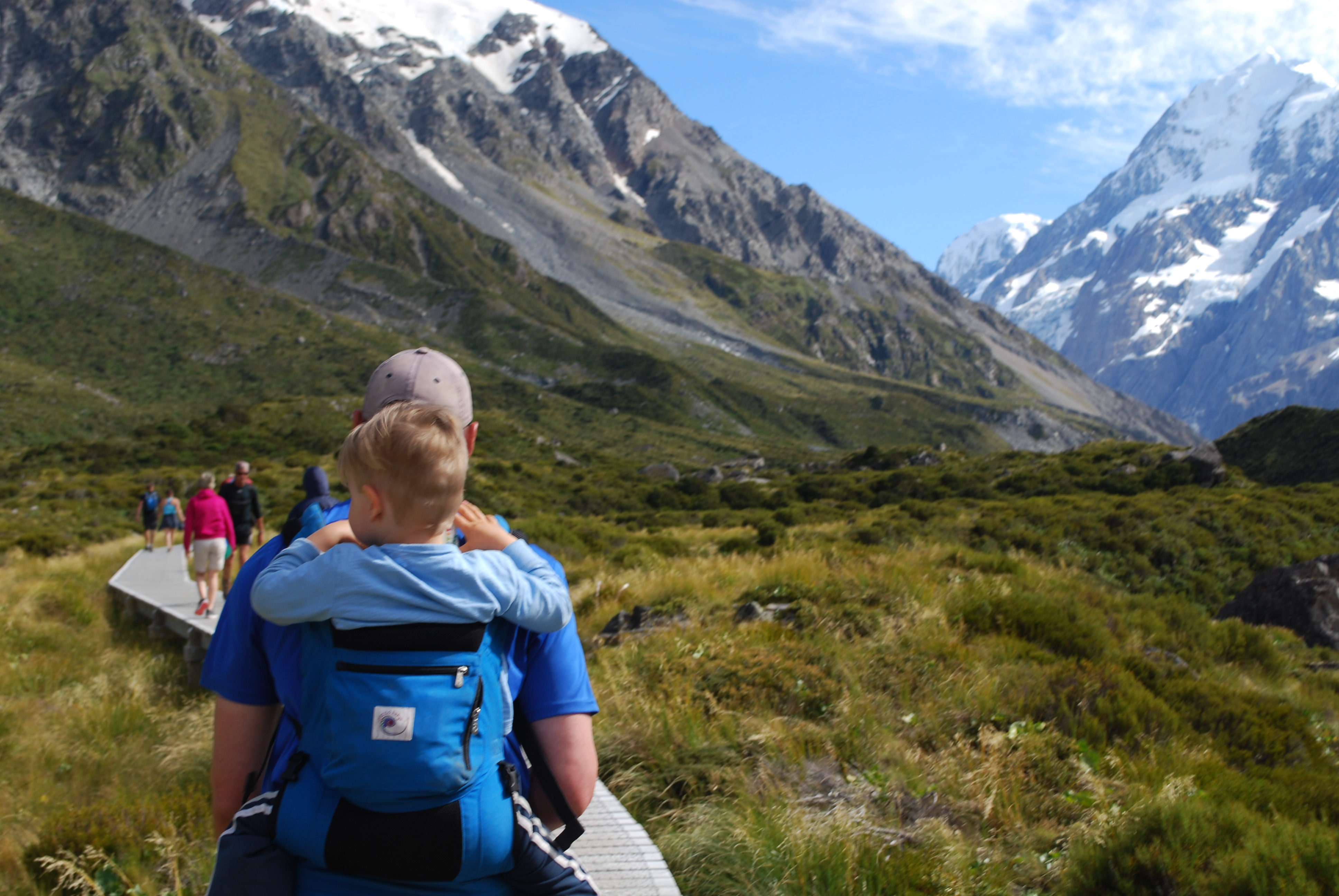 Ashley and Nathan, from Backyard Travel Family, packed in an Erogbaby backpack, trek the Hooker Valley Track in late Summer, Mt Cook National Park, New Zealand