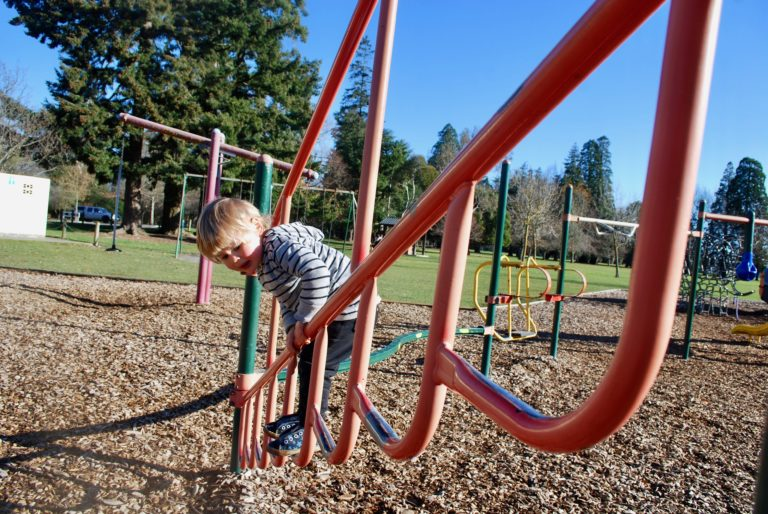 Nathan from Backyard Travel families tests out the climbing frame at the Ashburton Domain Playground