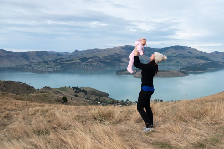 Jennifer from Backyard Travel Family lifts baby Emilia, while overlooking Banks Peninsula from the Rapaki Track Walk, Christchurch, Canterbury