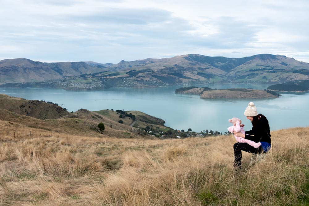 Jennifer from Backyard Travel Family spends quality time with baby Emilia, while overlooking Banks Peninsula from the Rapaki Track Walk, Christchurch, Canterbury