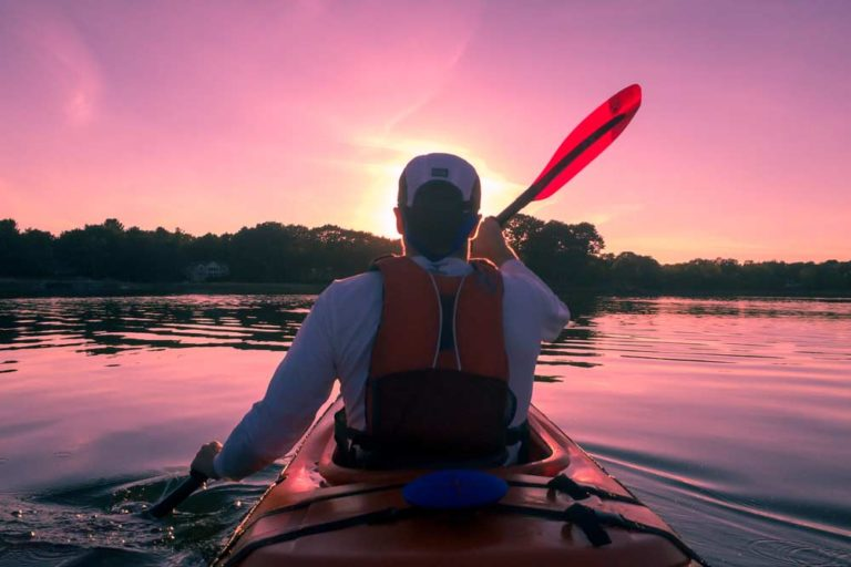 Kayaker at sunset. To find out the cost of these types of activities, check out our Cost of Travel in New Zealand article I Backyard Travel Family