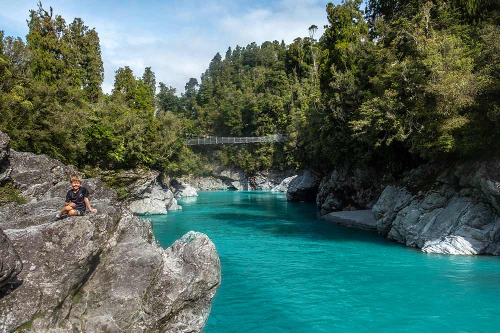 Nathan from Backyard Travel Family sits on a rock with the Hokitika Gorge Walk swingbridge in behind. The azure blue/green waters are glistening in the sunlight