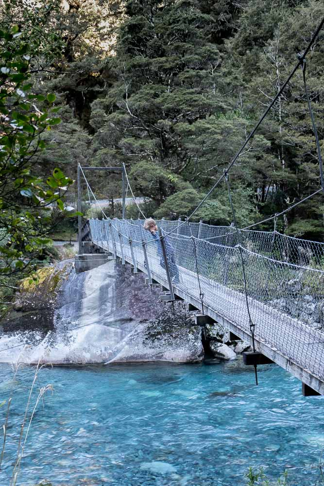 Nathan from Backyard Travel Family viewing the crystal clear water at the start of the Lake Marian Track. A great walk to the Marian Falls, crossing the swingbridge. A lovely short walk with kids