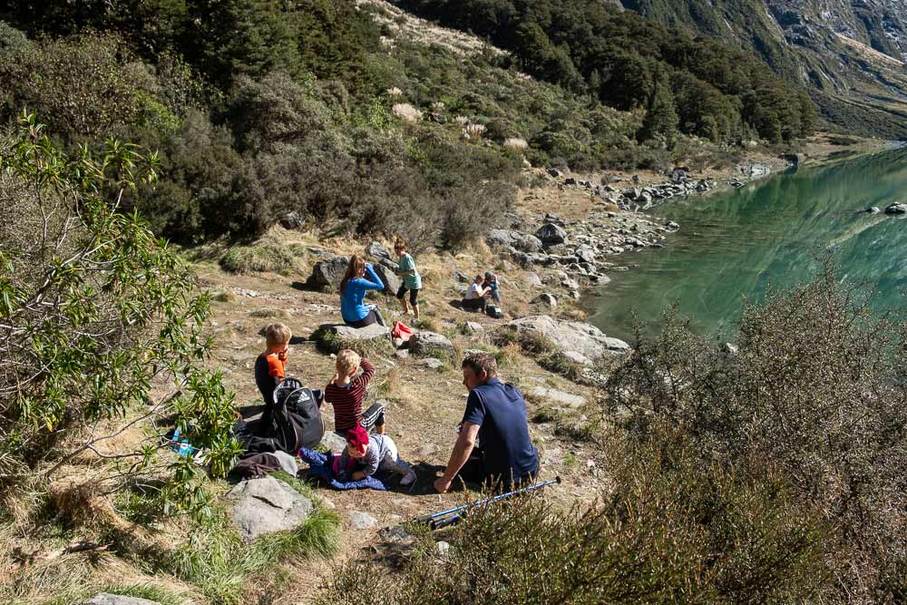Sitting beside the beautiful Lake Marian, on the Lake Marian track, a great half way walk on the Milford Road Highway, Fiordland. You can even walk to Lake Marian with kids by Backyard Travel Family