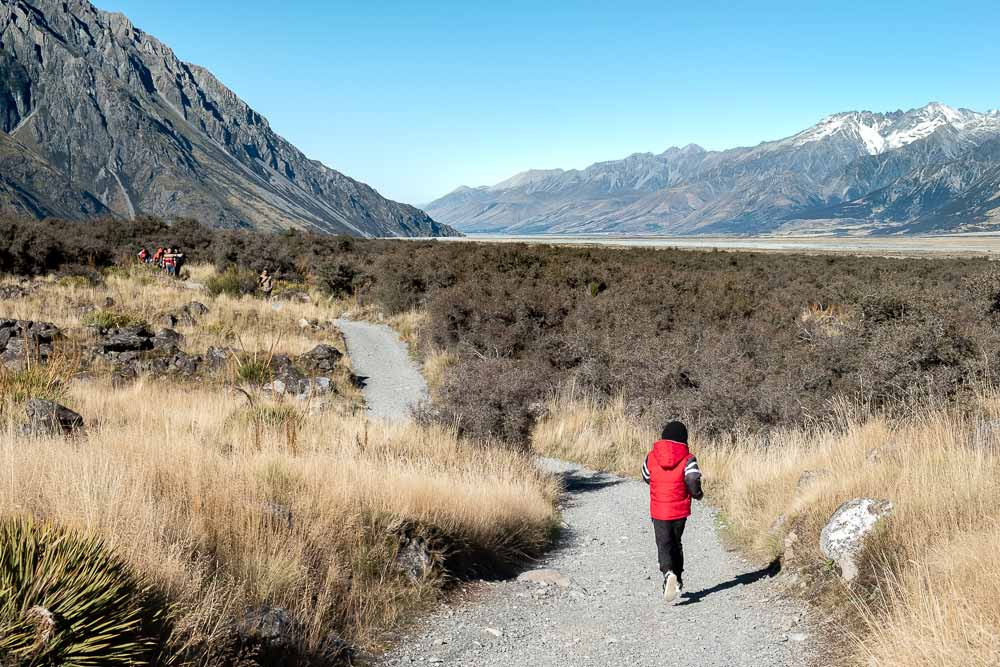 Nathan from Backyard Travel Family jogs on the Tasman Glacier Lake track, overlooking Mt Cook National Park, the perfect short walk for families with kids