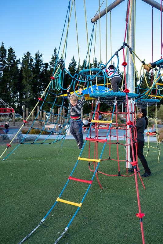 Kipton from Backyard Travel Family jumps off the rope climbing frame at Foster Park Playground, Rolleston, Christchurch, New Zealand