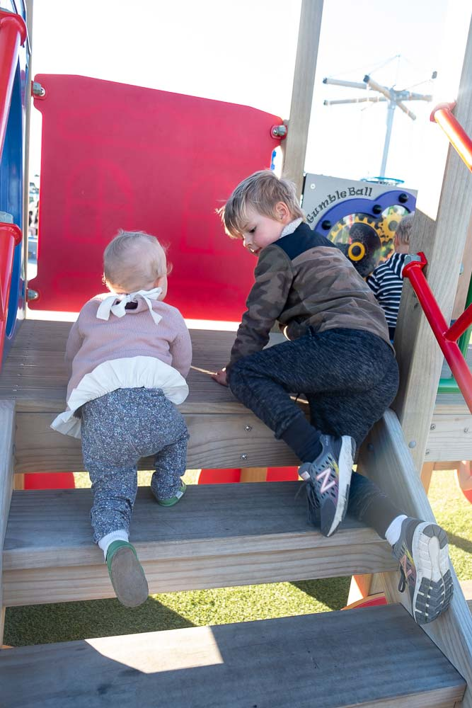 Nathan helps Emilia from Backyard Travel Family negotiate the stairs in the under 5s area of Rolleston's Foster Park Adventure Playground, Christchurch, New Zealand