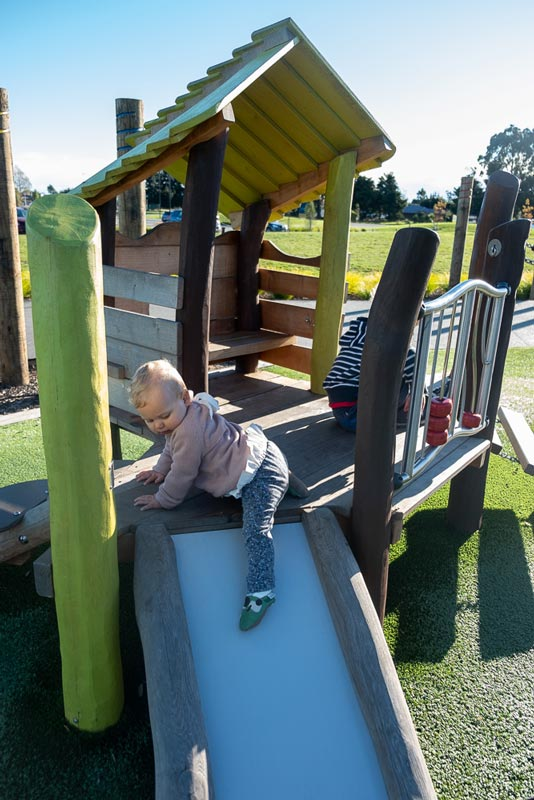 Emilia from Backyard Travel Family tests out the slide in the toddlers area of the Foster Park Playground, Rolleston, New Zealand