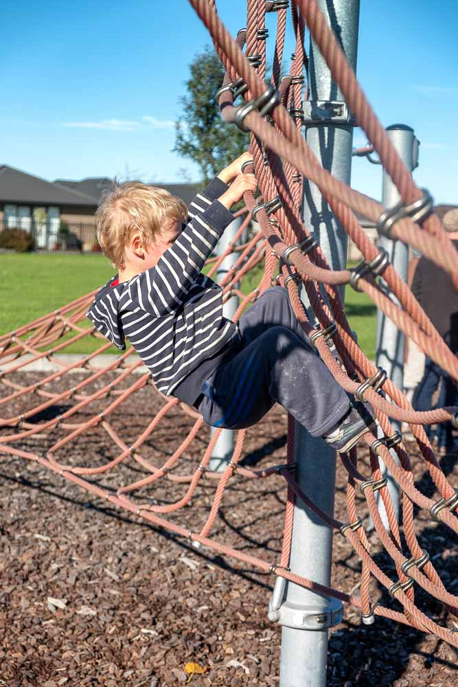 Kipton from Backyard Travel Family climbs the rope structure at Neil Graham Park Playground, next to Knights Stream School, Halswell, Canterbury, NZ