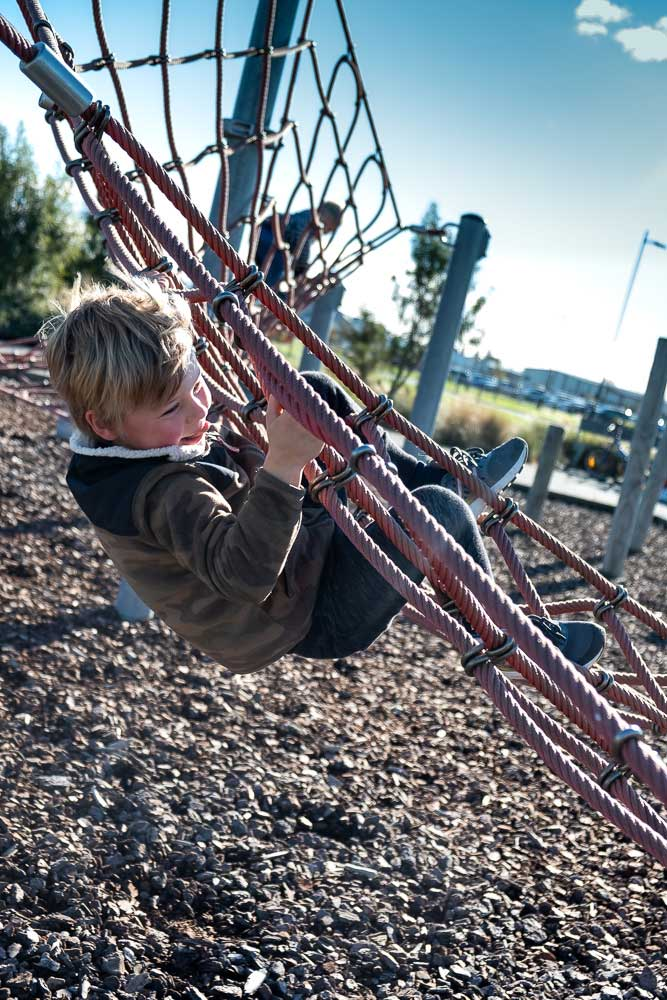 Nathan from Backyard Travel Family clings onto the rope climbing structure at Neil Graham Park Playground, Halswell, Christchurch, New Zealand