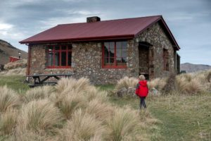 Kipton from Backyard Travel Family checks out the historic Packhorse Hut, looking over Banks Peninsula, Christchurch, NZ