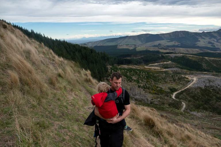 5 minutes from Packhorse Hut, Ashley from Backyard Travel Family carries 3 year old Kipton on the narrow ridgeline track // Packhorse Hut Track, Canterbury, New Zealand