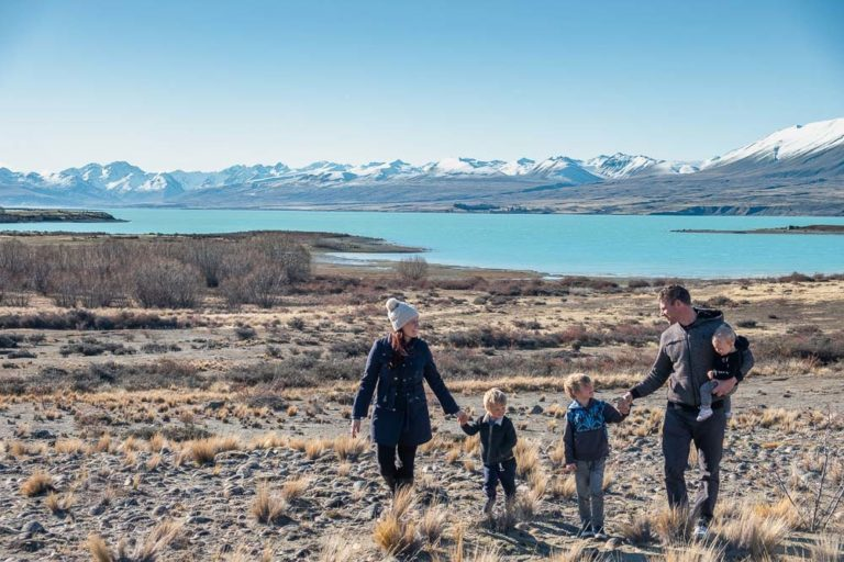 Backyard Travel Family walking hand in hand, checking out the many things to do in Lake Tekapo with kids in winter // Mackenzie Region, Canterbury, New Zealand