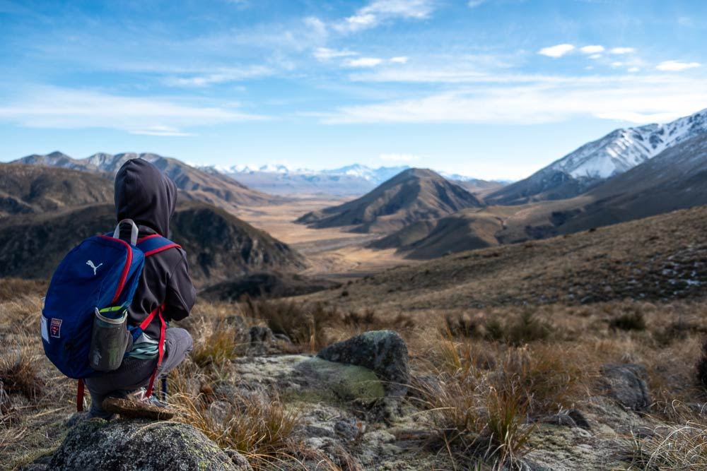 Nathan from Backyard Travel Family looks at the views towards the Ashburton Lakes, on the Woolshed Creek Hut Walk, best overnight hike for kids or half day walk, Mid Canterbury, New Zealand