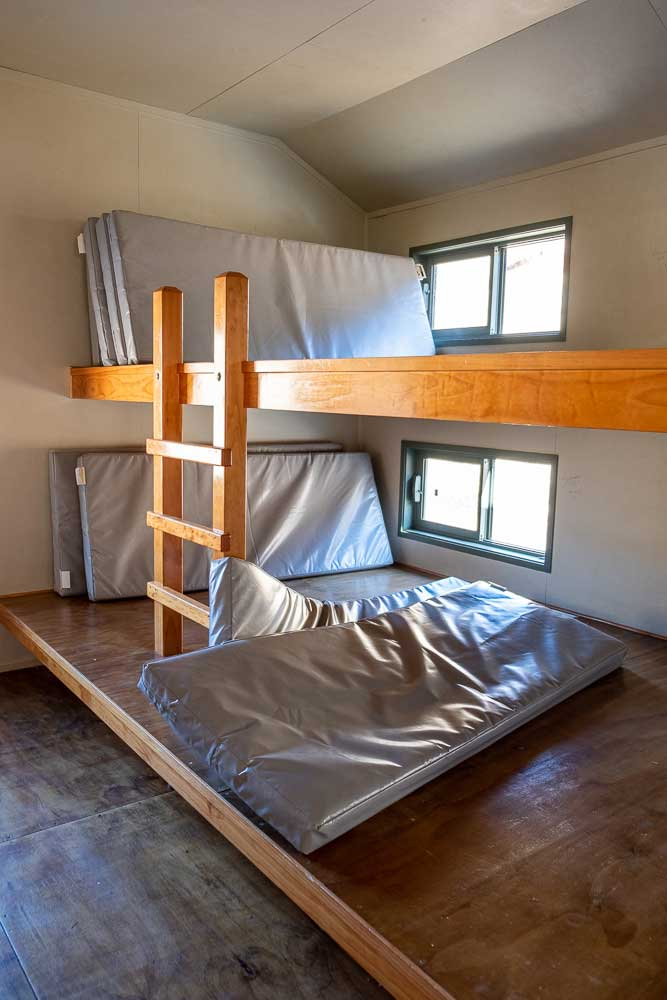 Bunk beds at Woolshed Creek Hut, Mt Somers Track. They are shared bunks with multiple mattresses lying side by side. Photo by Backyard Travel Family, New Zealand