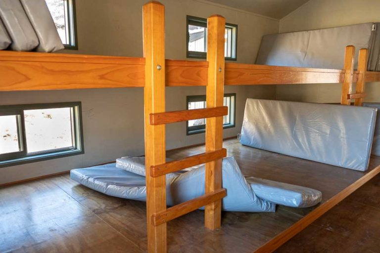 Close up of Bunk beds at Woolshed Creek Hut, Mt Somers Track. They are shared bunks with multiple mattresses lying side by side. Photo by Backyard Travel Family, New Zealand