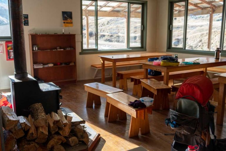 Dining area and log burner at Woolshed Creek Hut, Mt Somers Track. A great overnight hike for families or half day walk with kids