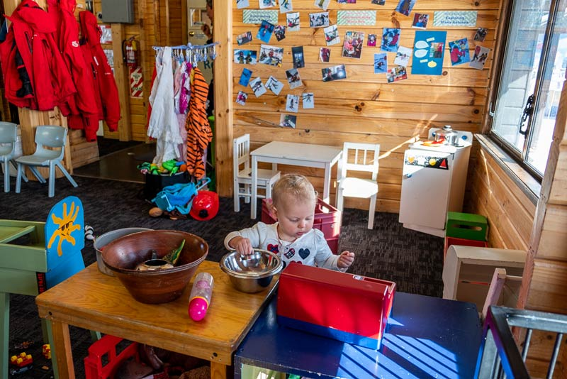 Wide angle of Skiwiland Preschool, inside Emilia plays with the cash register while her brother skis outside.