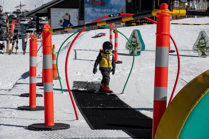 Kipton from Backyard Travel Family walks up the rubber mats in the Skiwi Kids group lesson at Mt Hutt Skifield, Canterbury, NZ