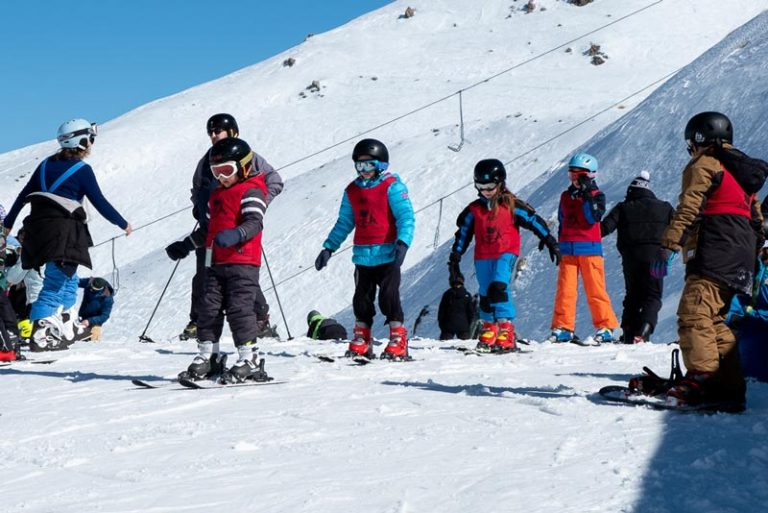 Nathan from Backyard Travel Family leads the Kea Club students on the learners slope at Mt Hutt Skifield, Methven, New Zealand