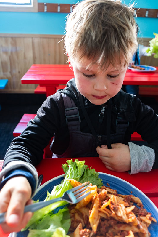 Nathan from Backyard Travel Family tucks into the delicious pasta meal with salad and fruit at his Kea Club Ski School Programme at Mt Hutt
