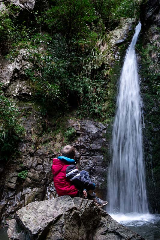 Nathan from Backyard Travel Family feels the spray on his face while sitting on a rock close to Washpen Falls, Methven, Canterbury