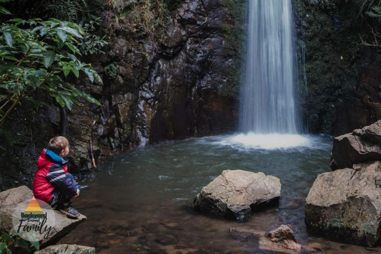 Nathan from Backyard Travel Family sits on a rock overlooking the beautiful Washpen Falls waterfall near Methven