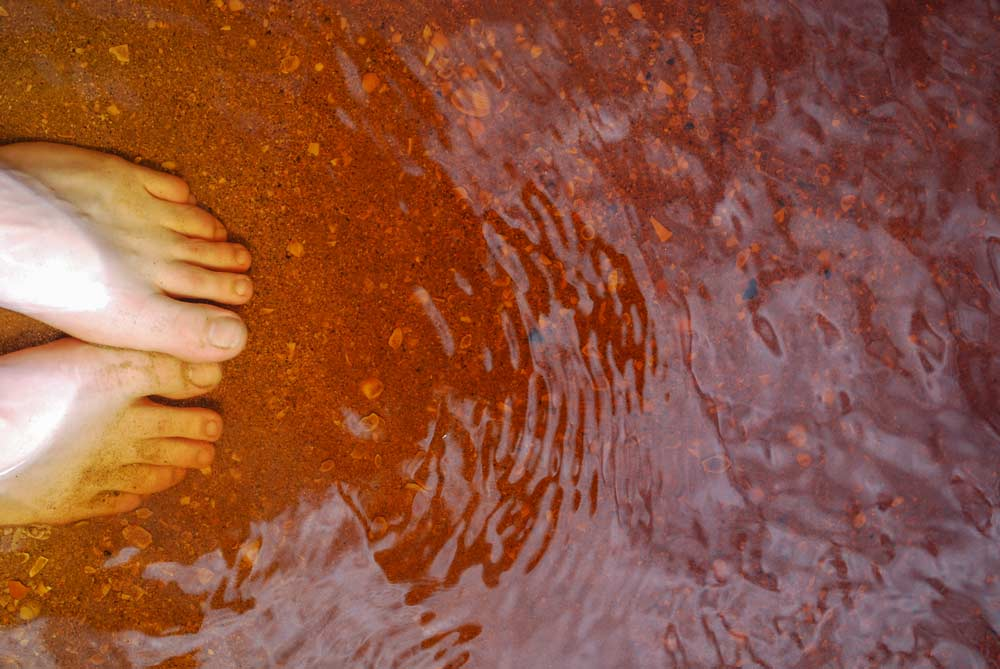Close up of bare toes, dipped into the red, orange water at Coca Cola Lake in Doubtless Bay