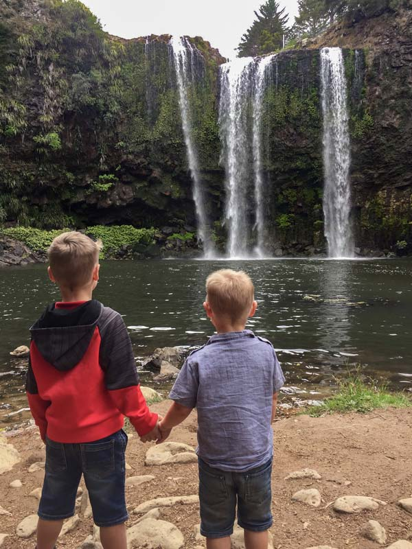Nathan and Kipton from Backyard Travel Family hold hands as they admire Whangarei Falls, Northland