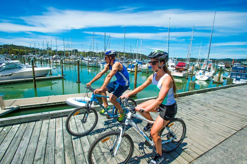 2 cyclists on the boardwalk in Opua on the Twin Coastal Cycle Trail, Northland