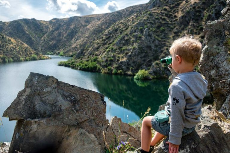 Kipton sits on a rock and uses his binoculars to look out over Deep Stream from the Deep Stream track, looking up the canyon. Lake Aviemore, near Kurow, Waitaki Region