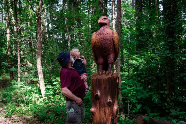 Grandad and Emilia from Backyard Travel Family check out the beautiful wooden eagle sculpture on the Forest Amble Walk