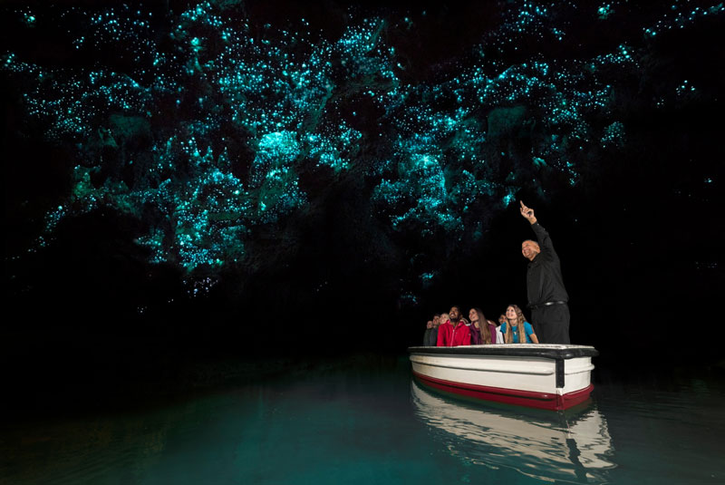 Tourists listening to a guide in the boat at the Glow Worms tour at Waitomo Caves