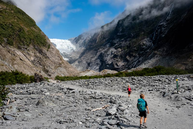 Nathan and Kipton from Backyard Travel Family walk on the Franz Josef Glacier track, as the cloud clears to reveal the icy white Franz Josef Glacier