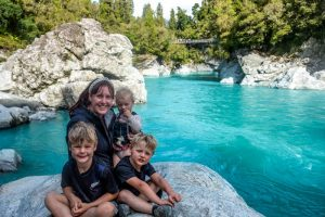 Backyard Travel Family sit on a rock at the Hokitika Gorge, with the swing bridge in the background. The crazy blue water shows that this really is one of the best things to do in Hokitka