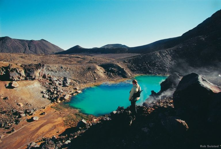 Tourist looks over at the Emerald Pools down below on the Tongariro Crossing hike; one of the best hikes in New Zealand's North Island