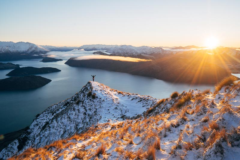 A person stands on the ledge of the Roys Peak Track at sunrise, sun peaking over the mountains, arms up in awe as they look at the mountains and Lake Wanaka below