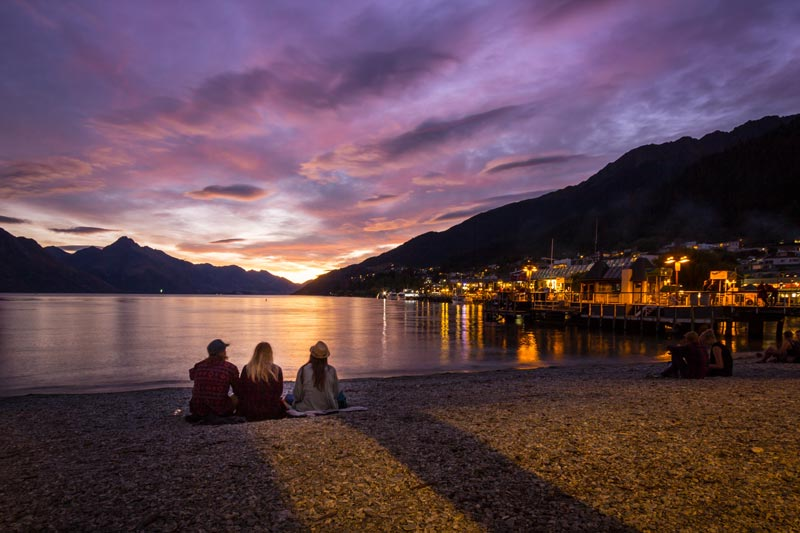 Tourists watch the sun go down on Queenstown Watefront at Sunset