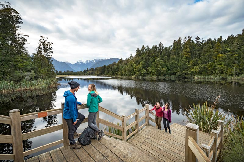4 adults enjoying the beautiful views on the Lake Matheson walk, West Coast, NZ. Photo by Miles Holden
