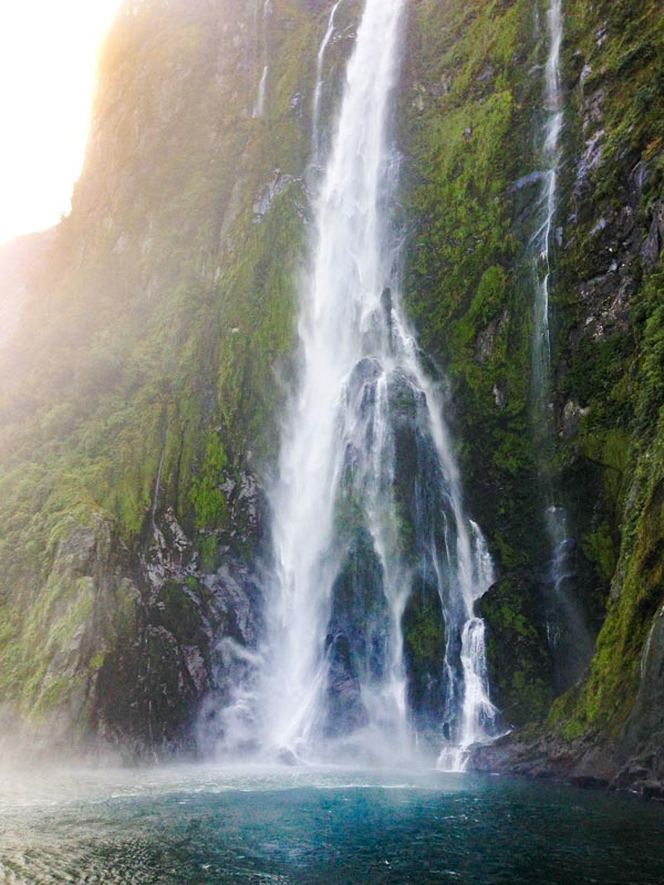 Powerful waterfall spills into the fjord on the Milford Sound Cruise