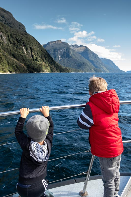 The boys lead on the boat railing, looking at the water on a beautiful day in Doubtful Sound