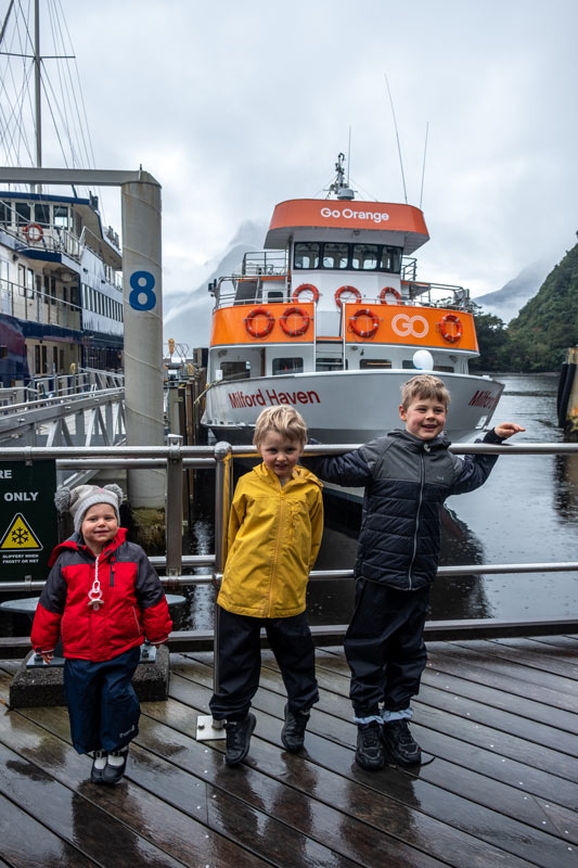 Backyard Travel Family kids stand in front of the Go Orange Milford Haven boat before a Milford Sound Cruise