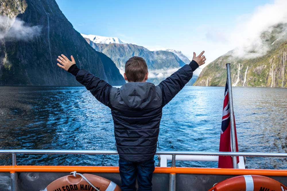 Nathan from Backyard Travel Family puts out his arms in excitement to be on the Go Orange Milford Sound Cruise