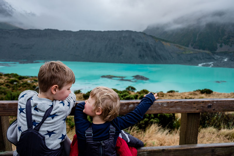 Backyard Travel Family kids smile at each other as they look at the turquoise Mueller Lake in Mt Cook National Park