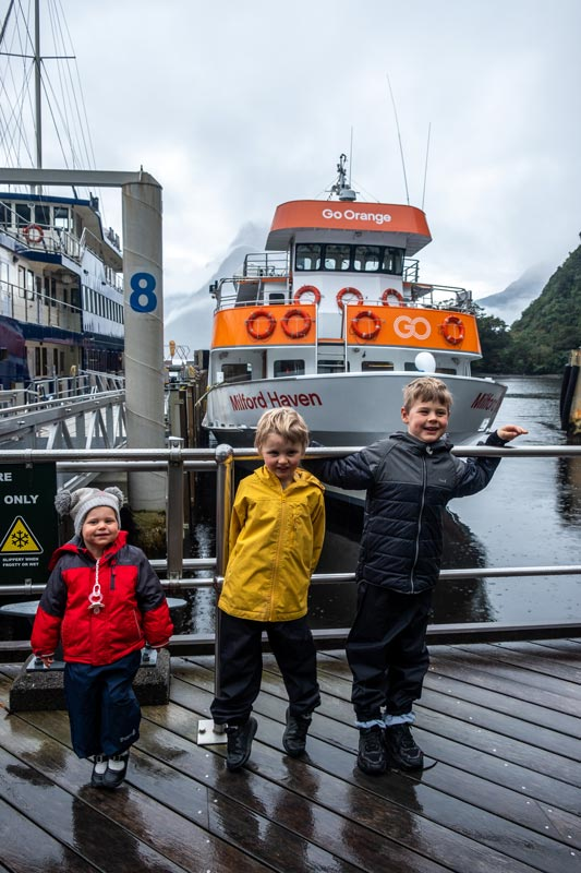 Backyard Travel Family kids stand in front of the Milford Haven at the dock, prior to their Milford Sound Cruise