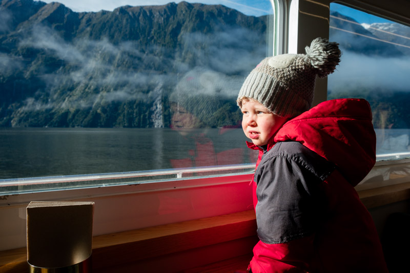 Emilia from Backyard Travel Family gazes out the window of the Milford Haven, watching the hundreds of waterfalls