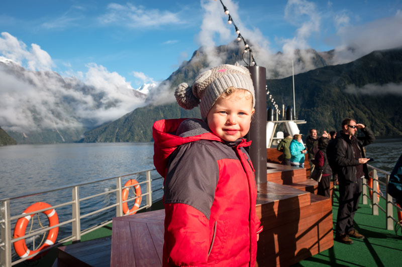 2 year old Emilia, standing on the top deck of Go Orange Milford Sound Cruise boat, looking at the amazing waterfalls