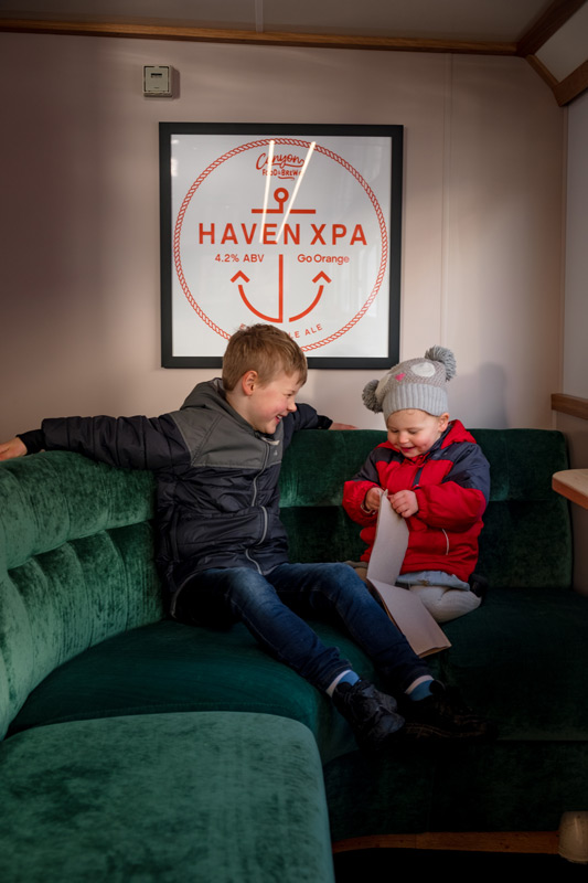 Nathan and Emilia from Backyard Travel Family sit on the green velvet couches onboard the Go Orange Haven Boat on their Milford Sound Cruise