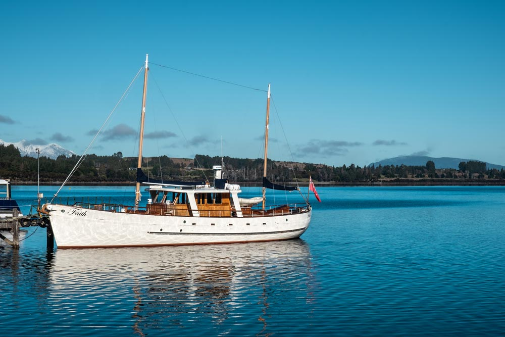 Faith in Fiordland Boat from Fiordland Historic Cruises: The boat sits on Lake Te Anau on a clear blue day