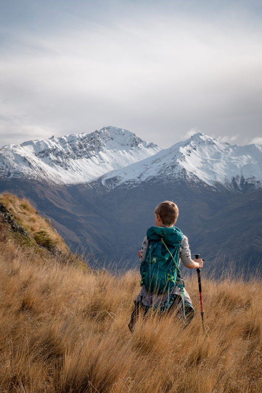 Nathan looks over the snow capped Southern Alps on the Rocky Mountain Wanaka hike
